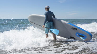 Young active person with inflatable stand up paddle board and oar in sea waves go surfing